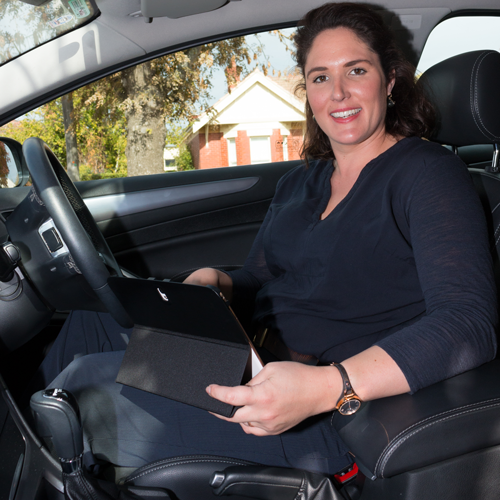 District Nurse in car with laptop
