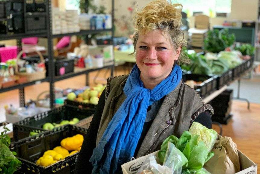 Lady holding box of lettuce
