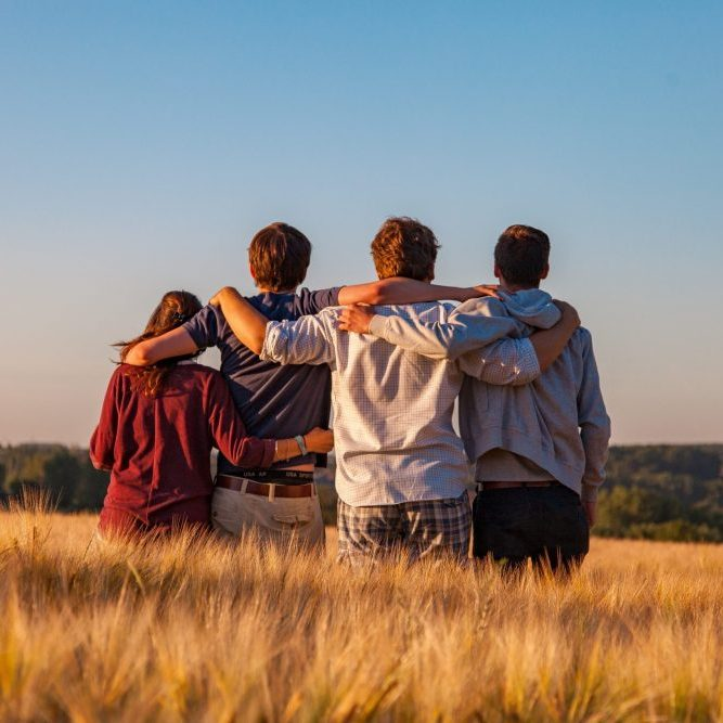 4 people embracing viewing scenery